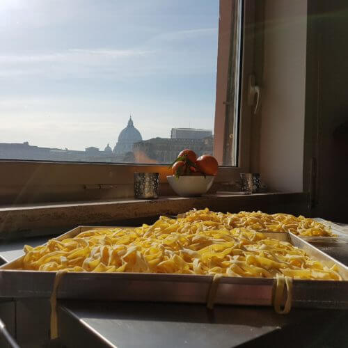 Trays of Fettuccine pasta with a view of the Vatican onthebackground