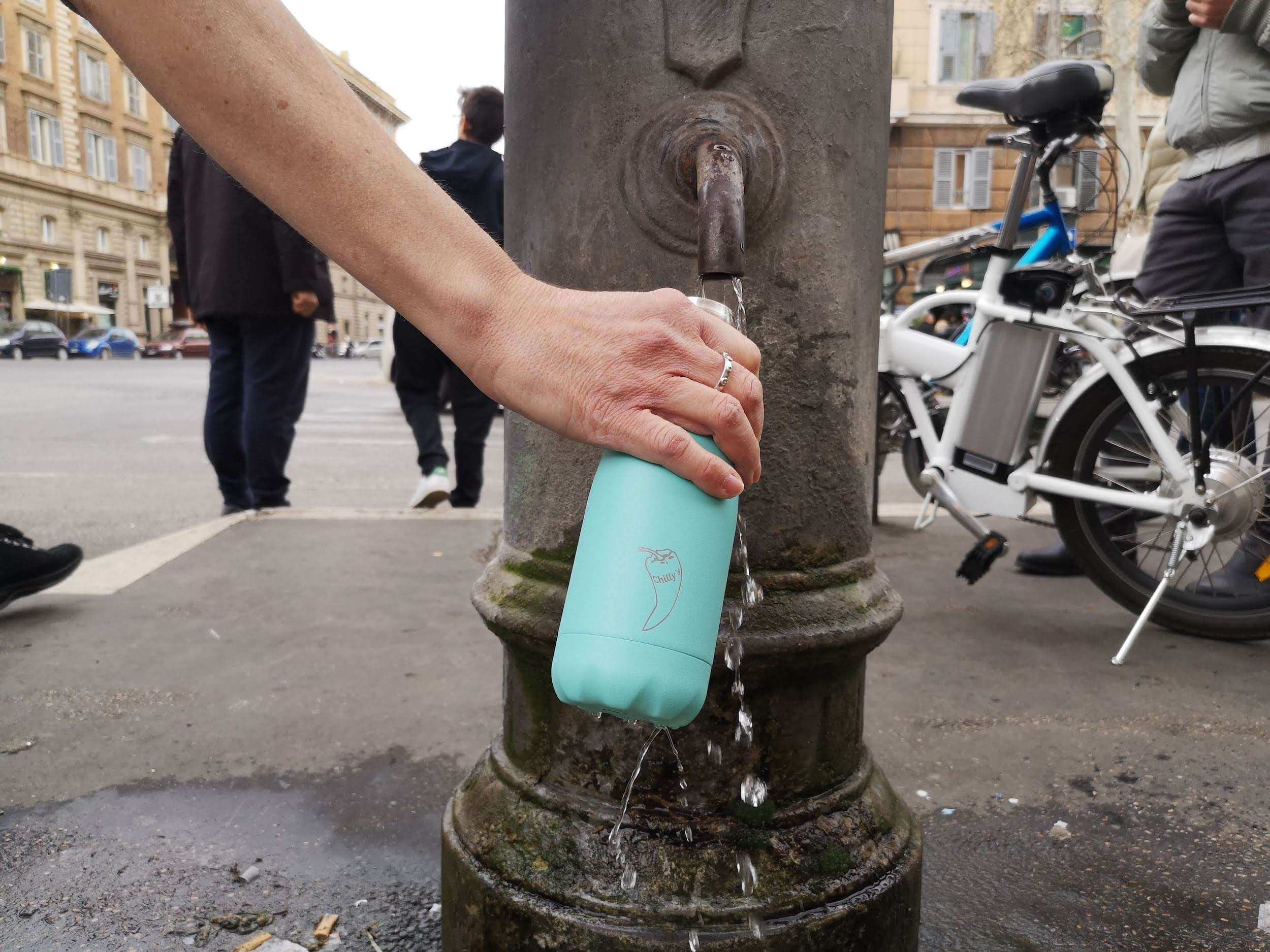 a person refilling a light blue chilly's bottle