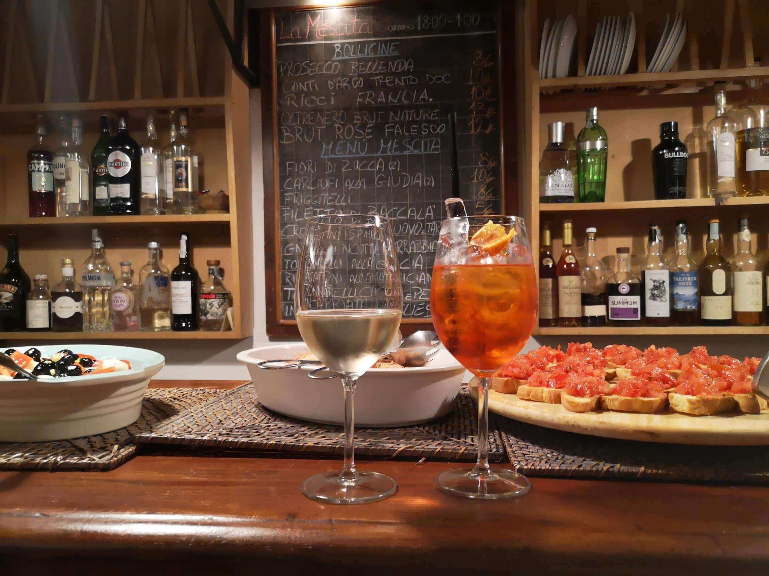 2 glasses, one with prosecco and one with spritz, on a counter with fingerfood on the background