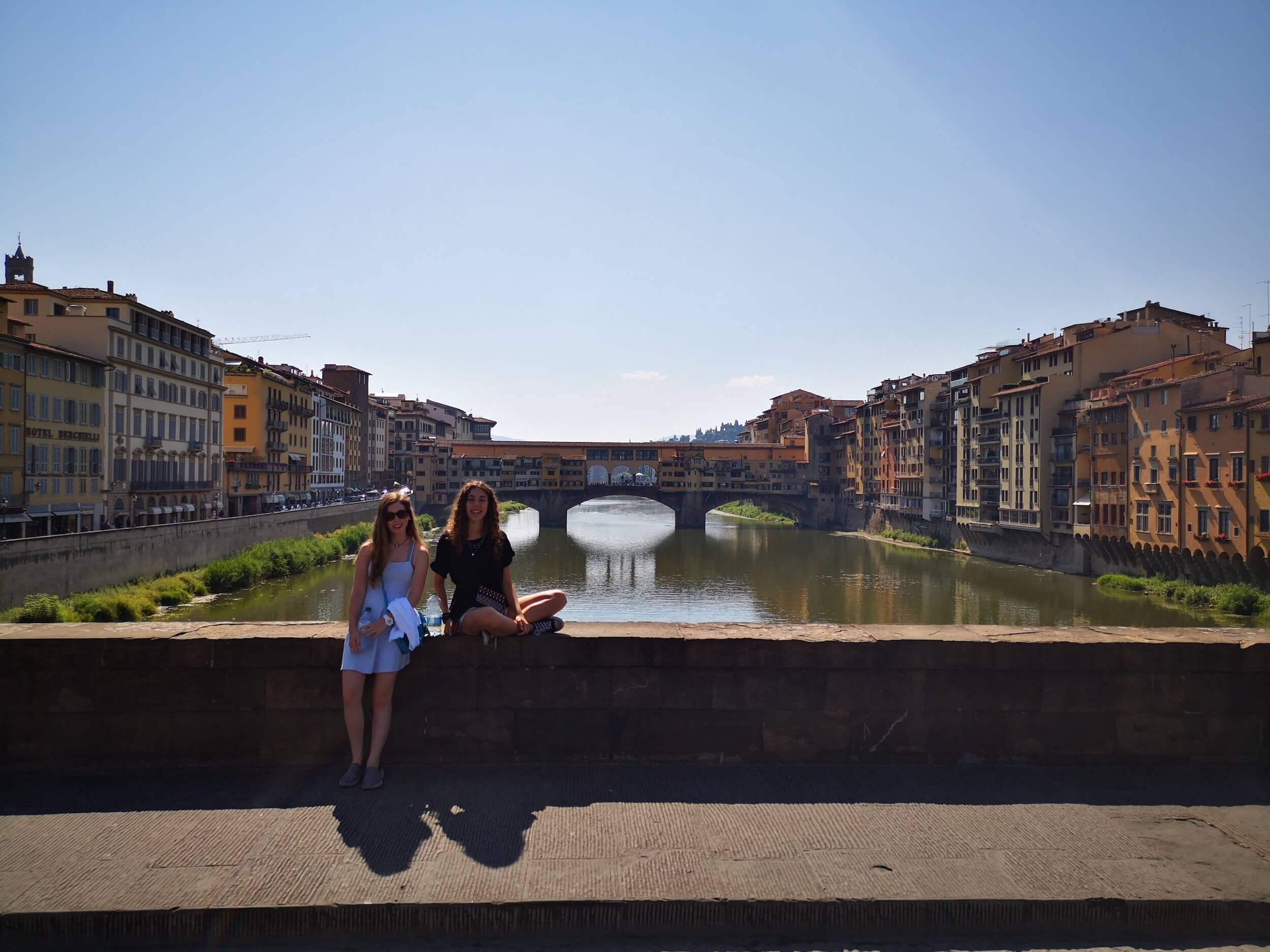 Two girls sitting on a bridge in Florence